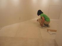 黒いカーペットの上に白い石で出来た床を張ります(藤井保展)